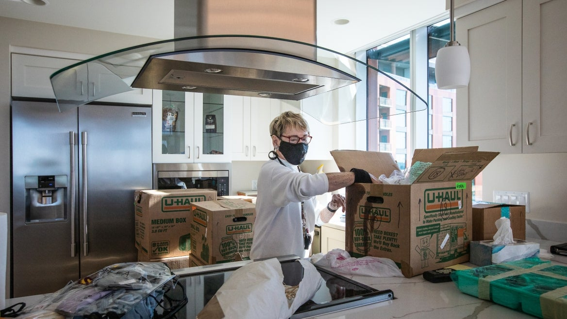A woman in a mask unpacks boxes in her new kitchen