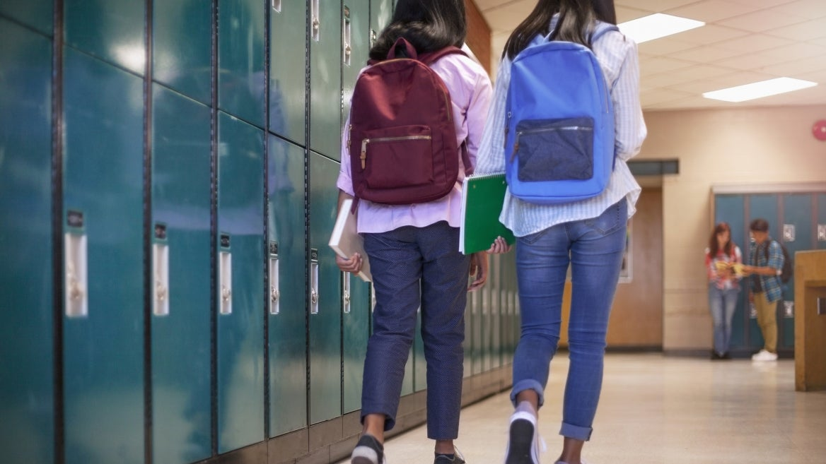 Two middle schoolers are shown from behind walking down a locker lined hallway