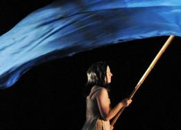 Theatre performance, female carrying a blue flag