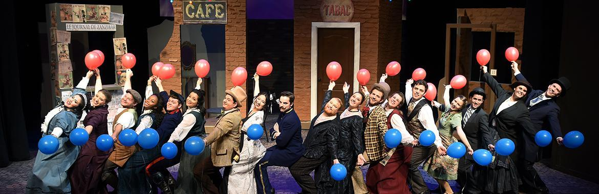 Actors on stage holding balloons
