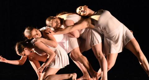4 dance performers leaning on each other.