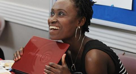 Theatre student smiling and holding a laptop